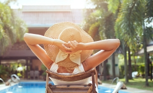 אישה יושבת על שפת בריכה במלון (צילום: Ditty_about_summer, Shutterstock)