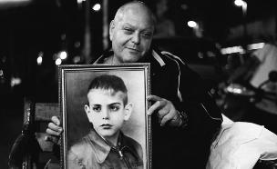 שושי לצד תמונתו כילד (צילום: מעין טפר)