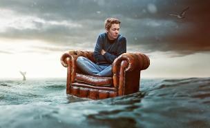 גבר מיואש על ספה בלב ים (אילוסטרציה: Shutterstock)