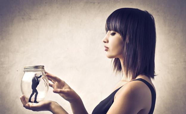 אישה מחזיקה גבר בצנצנת זכוכית (צילום: Shutterstock)