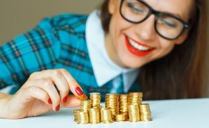 אישה עם ערימות מטבעות (אילוסטרציה: Shutterstock)