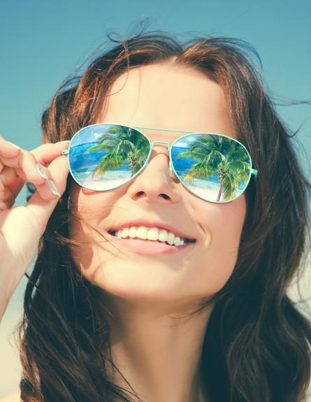 דקלים משתקפים במשקפי שמש של אישה (אילוסטרציה: Shutterstock)