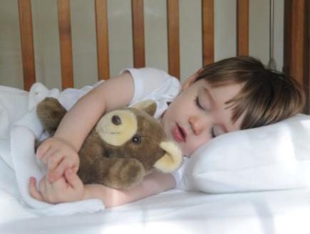 ילד ישן מחזיק בובה
