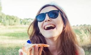 אישה אוכלת פיצה (צילום: tanja-vashchuk, Shutterstock)