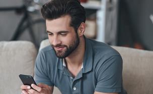 גבר מסתכל בטלפון (צילום: g-stockstudio, Shutterstock)