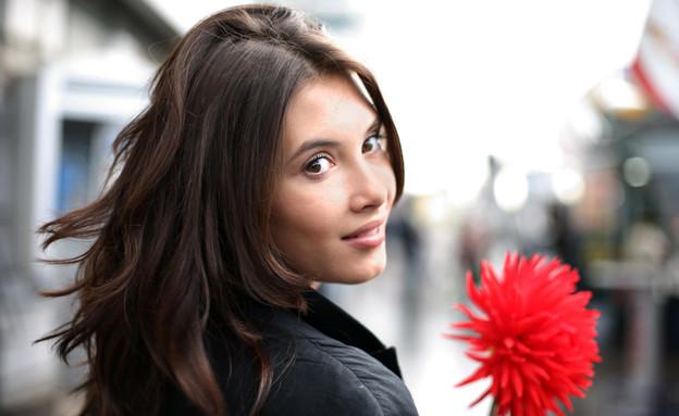 אישה שמחה עם פרח (צילום: Shutterstock, מעריב לנוער)