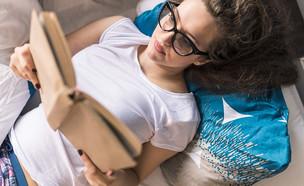 אישה קוראת ספר במיטה (אילוסטרציה: Shutterstock)