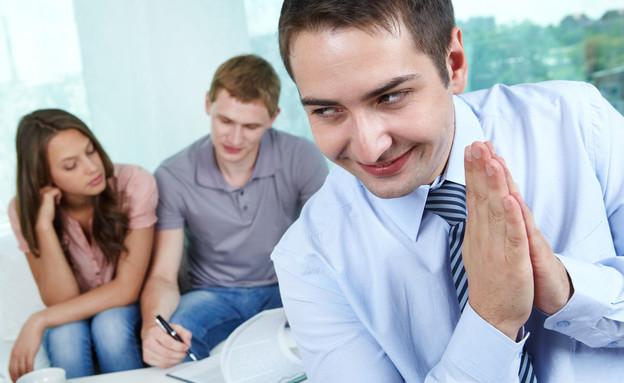 """מתווך נדל""""ן מרושע מחייך כשזוג חותם על חוזה (אילוסטרציה: Shutterstock)"""