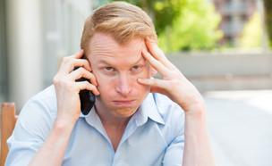 גבר מתוסכל מדבר בטלפון הסלולרי (צילום: Shutterstock)