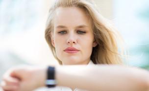 אשת עסקים מסתכלת על שעון יד (צילום: PKpix, Shutterstock)