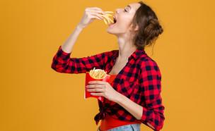 אישה אוכלת צ'יפס (צילום: Shutterstock)