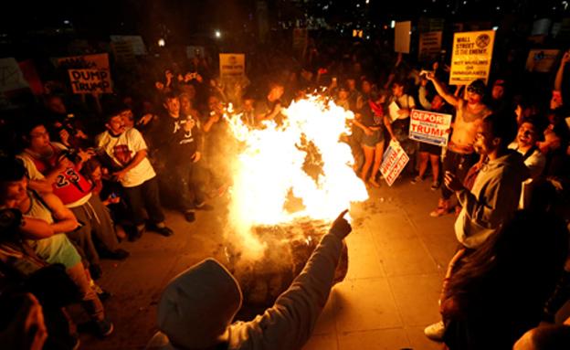 מפגינים שורפים פיניאטה בדמותו של טראמפ, (צילום: רויטרס)