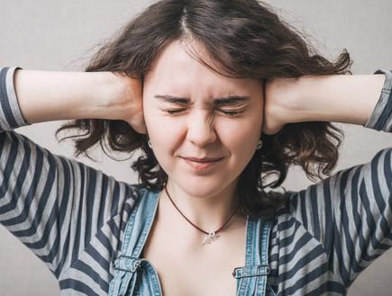 אישה מכסה אוזניים