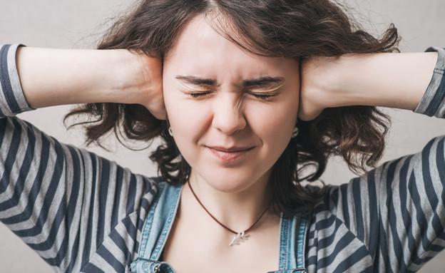 אישה מכסה אוזניים (צילום: file404, Shutterstock)