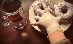 ילדה אוכלת סופגניות (צילום: Shutterstock)