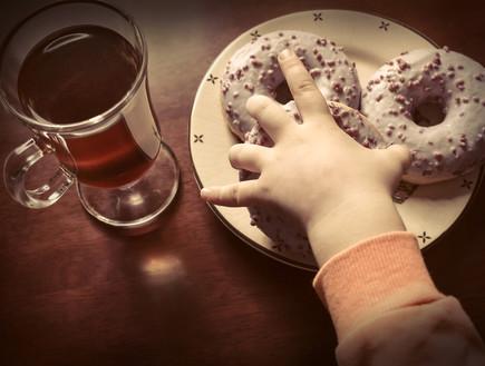 ילדה אוכלת סופגניות