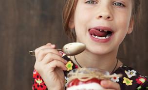 ילדה אוכלת יוגורט (צילום: Shutterstock)