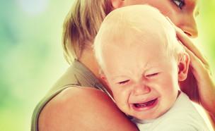 אמא מחבקת תינוק בוכה (צילום: Shutterstock)