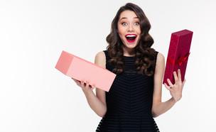 אישה מופתעת פותחת מתנה (אילוסטרציה: Shutterstock)