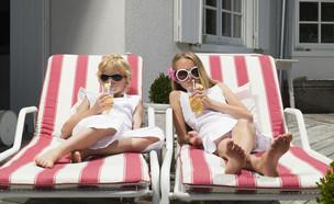 ילדות יושבות על כסאות נוח ושותות מיץ (אילוסטרציה: Shutterstock)