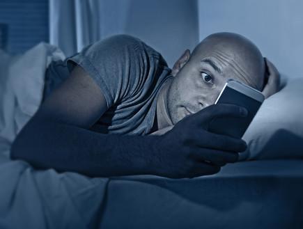 גבר בודק את הסלולרי באמצע הלילה (אילוסטרציה: Shutterstock)