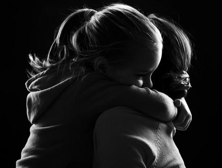 ילדה עצובה מחבקת את אמה