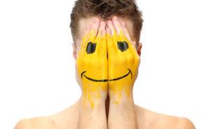גבר מסתיר את פניו בידיו עליהן מצויר סמיילי (צילום: ShutterStock)