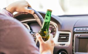 נהג עם בקבוק בירה ביד (צילום: ShutterStock)