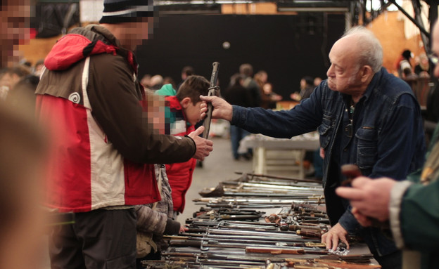 יריד אספנות נשק קר, זקן מראה חרב לאבא וילד (צילום: נועם גיגר)