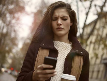 אישה כועסת מסתכלת על הטלפון שלה