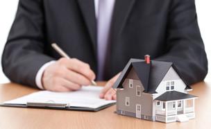 גבר חותם על מסמך ליד דגם של בית (אילוסטרציה: Shutterstock)