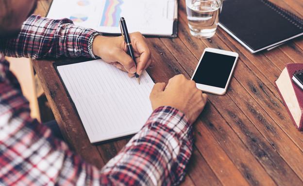 גבר כותב במחברת (אילוסטרציה: Shutterstock)