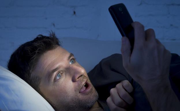 אדם צופה בסמארטפון (צילום: Marcos Mesa Sam Wordley, shutterstock)