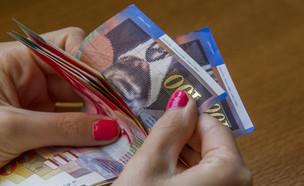 אישה סופרת כסף (צילום: Shutterstock)