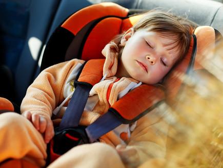 ילדה ישנה באוטו