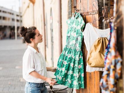 אישה בוחרת בגדים בחנות ביפו