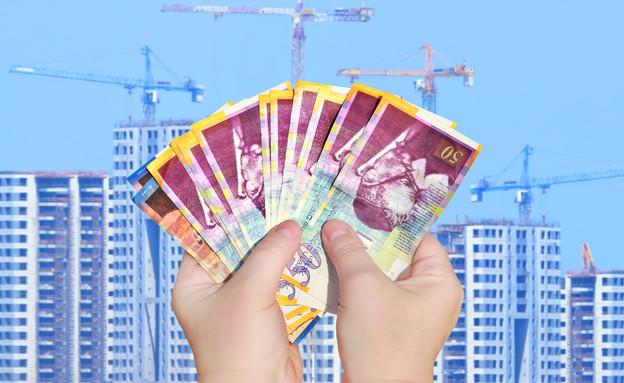 יד מחזיקה שטרות של 50 שקלים מול אתר בנייה (אילוסטרציה: Shutterstock)
