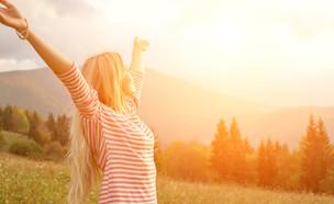 אישה שמחה בשקיעה (צילום: Shutterstock)