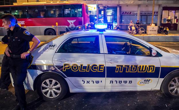 שוטר עומד ליד ניידת משטרה בתל אביב (צילום: Shutterstock)