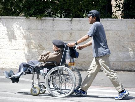 עובד פיליפיני מוביל זקן בכיסא גלגלים