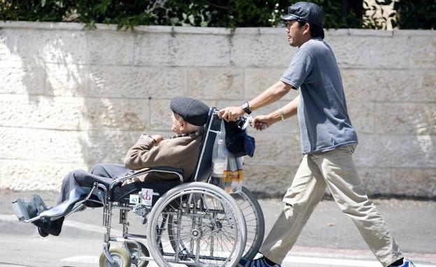 עובד פיליפיני מוביל זקן בכיסא גלגלים (צילום: אביר סולטן, פלאש 90)