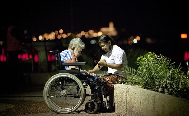 מטפלת פיליפינית עם קשישה בטיילת בתל אביב (צילום: משה שי לפלאש 90)