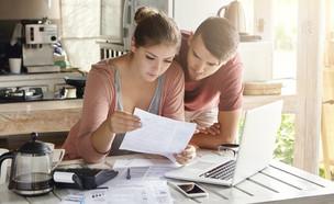 זוג צעיר בודק ניירת (אילוסטרציה: Shutterstock)