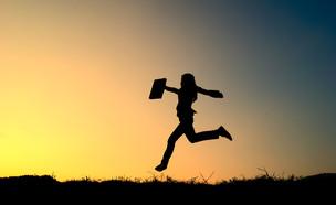 אשת עסקים קופצת מול השקיעה (אילוסטרציה: Shutterstock)