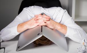 גבר מיואש מכסה את הראש עם מחשב (צילום: Kaspars Grinvalds, shutterstock)
