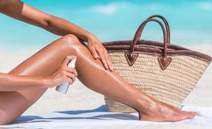 אישה מורחת שמן שיזוף (צילום: Maridav, Shutterstock)
