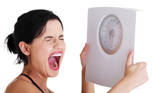 אישה מתוסכלת מחזיקה משקל (צילום: PhotoMediaGroup, Shutterstock)
