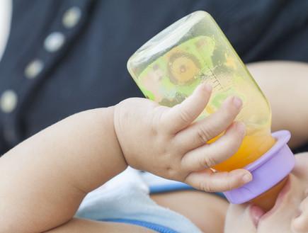תינוק שותה מיץ תפוזים