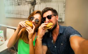 אוכלים המבורגר (צילום: Diana Indiana, Shutterstock)