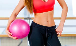 אישה מחזיקה כדור בחדר כושר (צילום: Satyrenko, Shutterstock)